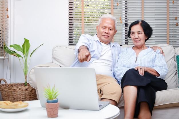 아시아 노인 부부가 집 거실에서 노트북으로 온라인 미디어를 시청합니다.