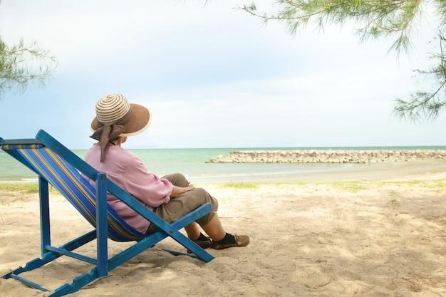 帽子をかぶった年配のアジア人女性がビーチのそばのデッキチェアに座っています。定年中の高齢者旅行の性質の概念。コピースペース