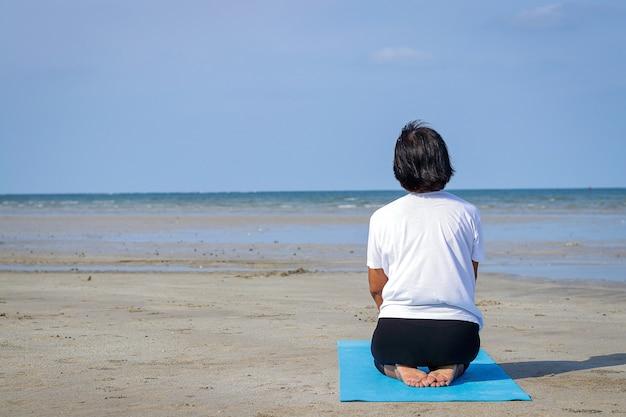 나이든 아시아 여성이 아침에 혼자 바다에서 요가를 하고 있습니다.