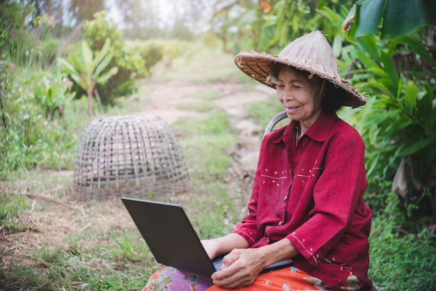 笑顔と幸せで農地の中でラップトップコンピューターを学び、使用する年配のアジア人女性