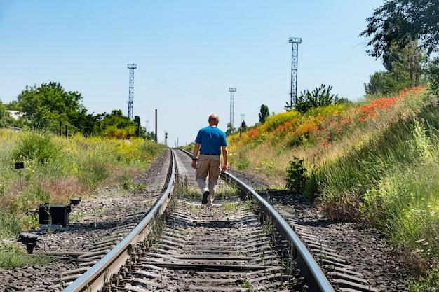 노인 대머리 남자가 양귀비와 함께 제방을지나 철도 트랙을 따라갑니다