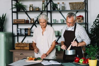 An elderly couple cooking vegetables in the kitchen