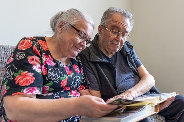 Пожилая пара рассматривает фотографии в семейном фотоальбоме.