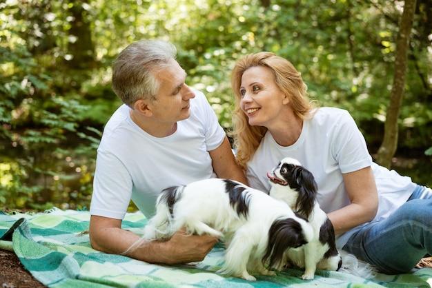 노인 부부는 숲에서 소풍에서 휴식을 취하고 담요에 개와 놀고 있습니다.