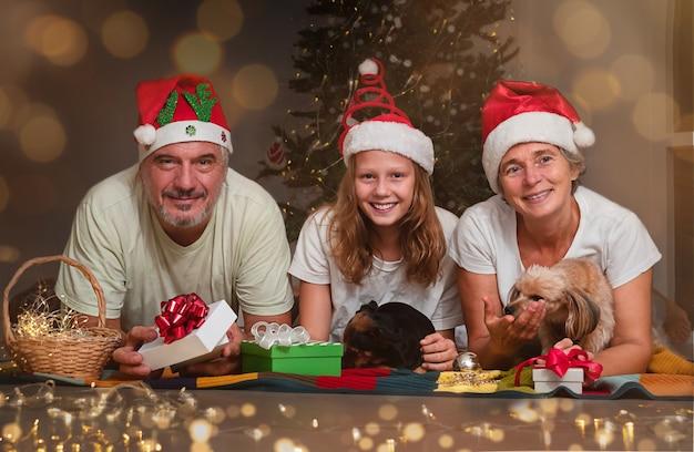 십대와 함께 노부부가 크리스마스 선물을 교환합니다. 크리스마스 트리 근처의 행복한 가족 초상화