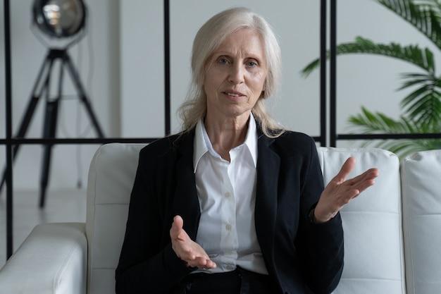 Пожилая женщина-бизнесвумен сидит на диване. зрелая женщина смотрит на жесты камеры и разговаривает онлайн во время видеозвонка