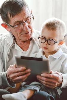 노인 할아버지와 그의 어린 손자가 함께 태블릿 장치를 사용하고, 웃고 즐겁게 지내거나, 인터넷에서 재미있는 비디오를 보고 의자에 앉아 있습니다.