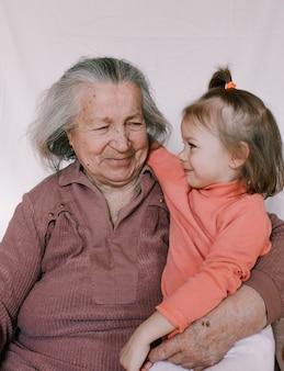 노인 할머니는 주름진 팔에 아름다운 소녀를 안고 있습니다. 가족 세대. 젊음과 노년. 어르신