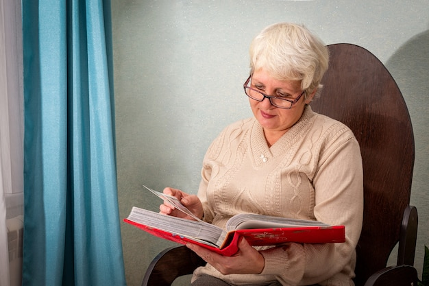 Пожилая дама в очках сидит дома в кресле, смотрит альбом с фотографиями и улыбается.