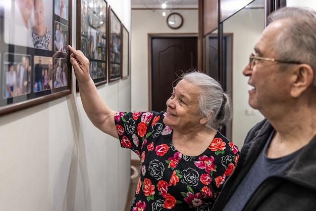 Пожилые мужчина и женщина рассматривают семейные фотографии.