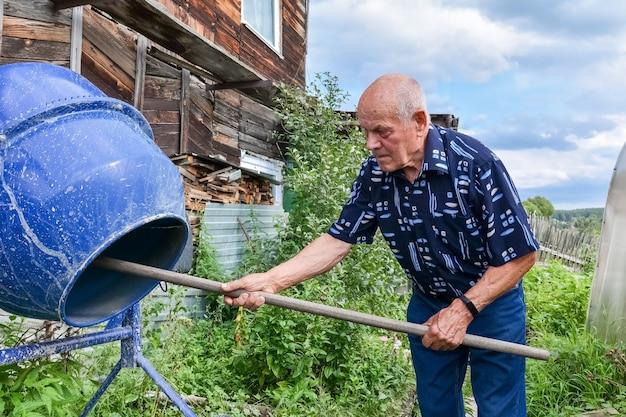 Пожилой мужчина чистит бетономешалку после строительных работ