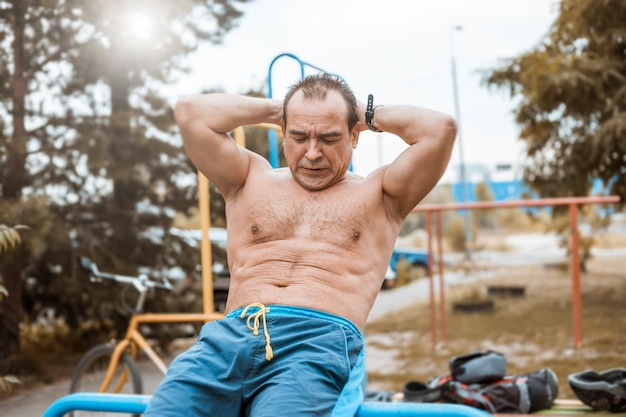 老人が腹筋を鍛える運動をしている。