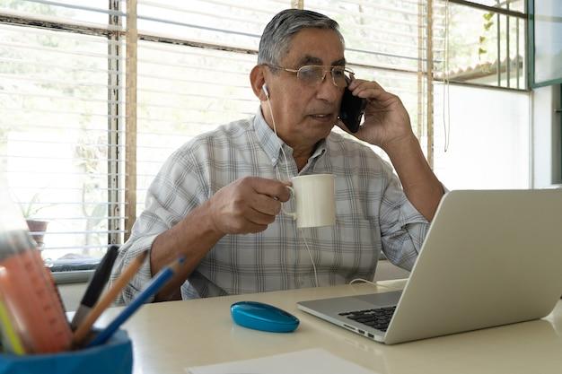 Пожилой мужчина сидит за ноутбуком пьет чашку кофе.