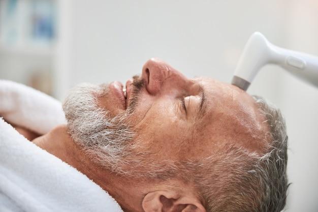 Пожилой мужчина лечит кожу лица в салоне красоты