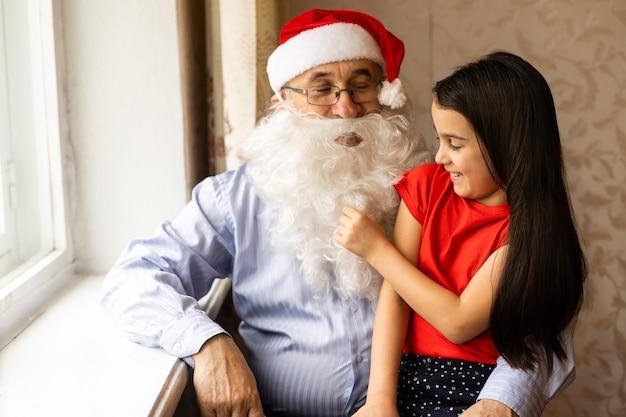 Пожилой мужчина в новогодней шапке и внучка