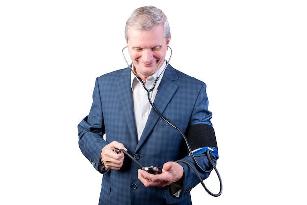 양복을 입은 한 노인이 손 안압계로 스스로 압력을 측정하고 있습니다. 흰색 배경에 고립. 어떤 목적을 위해.