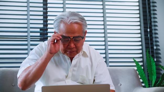Пожилой мужчина читает новости с планшета на диване у себя дома. пожилой азиатский мужчина ищет информацию в интернете, сидя в гостиной.