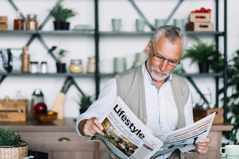 An elderly man reading newspaper