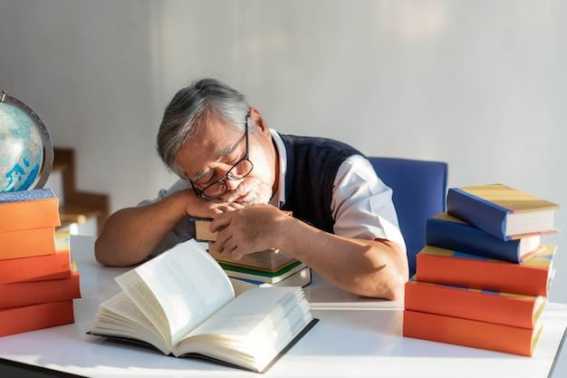 한 노인이 책상에서 읽고 있던 책을 보고 사무실에서 낮잠을 자고 있습니다. 그가 읽어야 했던 많은 책들이 여전히 그의 책상 위에 놓여 있었다 - 라이프스타일 노인 개념