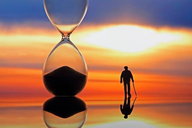砂時計の隣で夕日に向かって歩く老人。