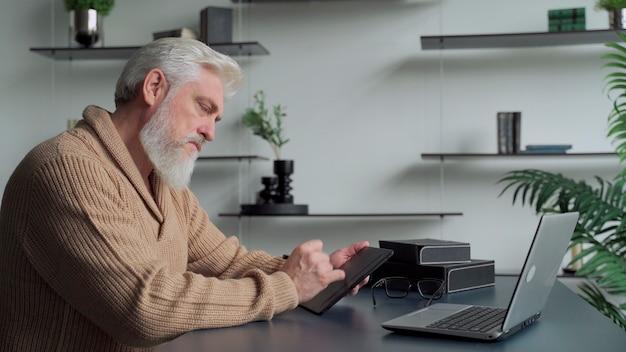 Пожилой мужчина с седой бородой рисует ручкой на планшете дома в гостиной