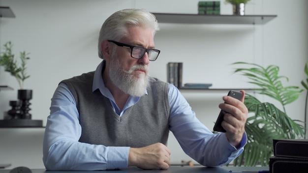 Пожилой мужчина с седой бородой пользуется смартфоном в офисе