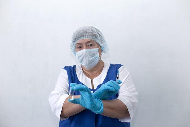 Пожилая медсестра держит шприц и ампулу, вакцинация
