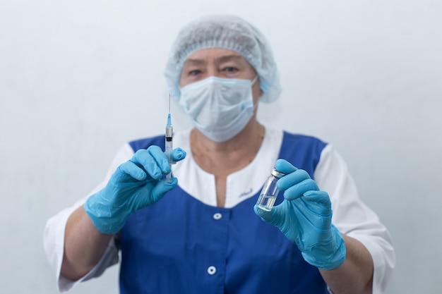 Пожилая медсестра держит шприц и ампулу