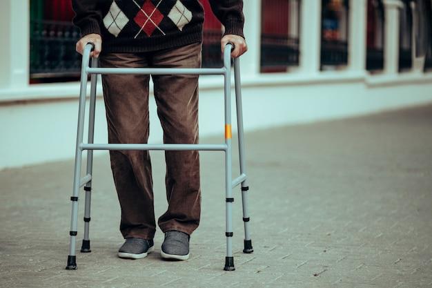Пожилой человек использует ходунки для прогулок по городу. ортопедическая поддержка при травмах ног и помощь инвалидам