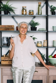 An elderly senior woman with cell phone standing in front of shelf