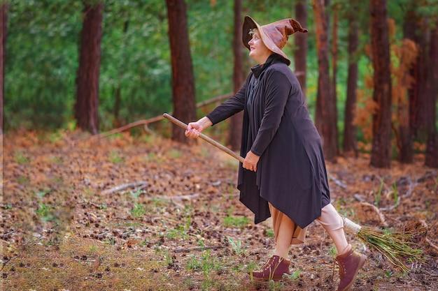 ほうきに座って、森の中で帽子をかぶった年配の魔女が飛びたいと思っています。