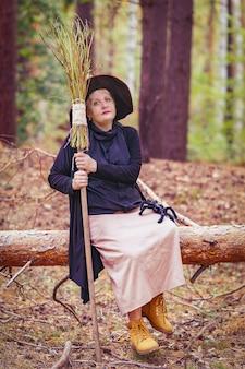 森の中で帽子をかぶった年配の魔女が、木の幹に座って、足を張り出し、ほうきを持って、蜘蛛が膝を這っています。