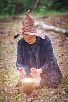 森の中で帽子をかぶった年配の魔女が地面に座って、ベニテングタケで魔女のポーションを醸造しています。