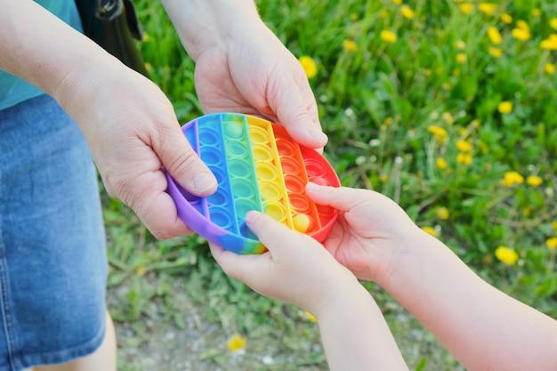 스트레스 해소 장난감을 들고 있는 노부인과 아이가 거리에서 그것을 팝니다. 배경에는 풀이 있습니다