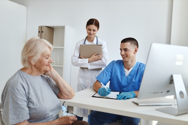Пожилая женщина на приеме у врача и помощница сестры, общение