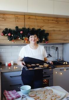 クリスマスのおやつを準備している台所で家にいる年配の女性。家族の伝統。