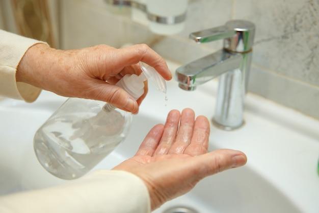 Пожилая женщина дезинфицирует руки в ванной