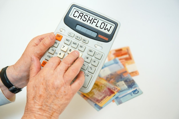 Пожилая женщина держит в руках калькулятор. надпись калькулятора - денежный поток.