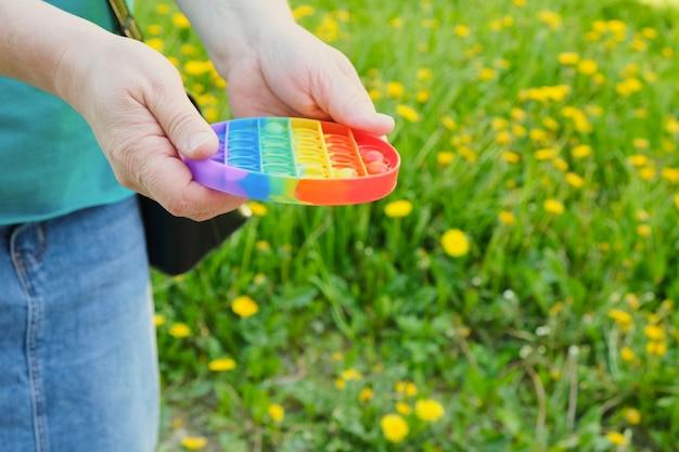 한 노부인이 스트레스 해소 장난감을 손에 들고 거리에 팝니다. 배경에는 잔디가 있습니다