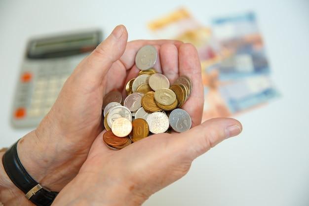 노인 여성은 그녀의 손에 많은 다른 동전을 보유