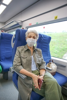 緑のジャケットと医療用マスクを身に着けた年配の女性が電車に乗る
