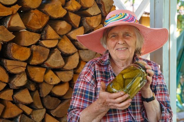 ピンクの帽子をかぶった年配の女性がきゅうりの瓶を持っています。手作りきゅうりの缶詰。