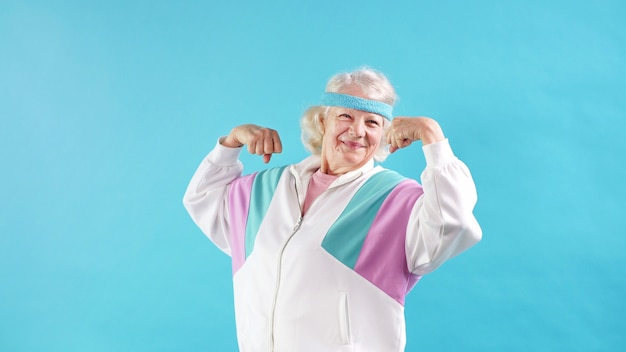 Пожилая женщина в спортивном костюме позирует