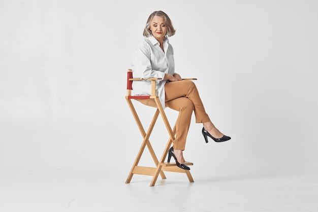 Пожилая женщина в белой рубашке сидит на стуле и позирует