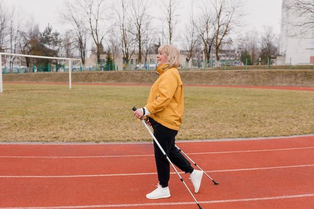 黄色のスポーツジャケットを着た年配の女性が、スタジアムのゴム製トレッドミルでノルディックウォーキングを屋外で練習しています。晴れた夕日。年金受給者の健康的なライフスタイル