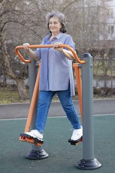 신선한 공기를 마시며 할머니가 운동을 하고 있는 시뮬레이터에서 스포츠를 하러 가는 노부인