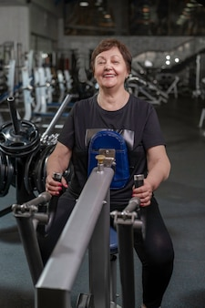 Пожилая женщина в тренажерном зале выполняет становую тягу в горизонтальном блоке