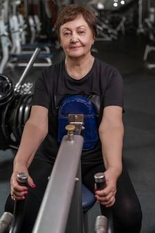 Пожилая женщина занимается фитнесом в тренажерном зале