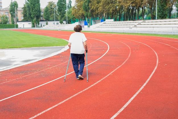 한 노인 여성이 경기장에서 막대기로 걷고 있습니다. 노르딕 워킹