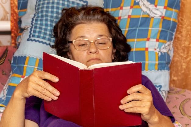 聖書を読んでいる年配の女性がベッドに横たわっています